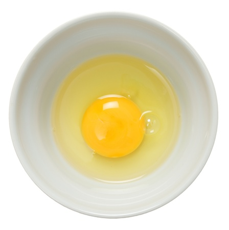 broken egg: An egg broken into a bowl and seen from above over a white background