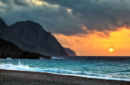 neighbouring: The sun dips below threatening clouds at sunset in Sougia, a small and fairly inaccessible town on the south coast of Crete, Greece   Cut off from neighbouring areas by the soaring mountains of Sfakia, Sougia