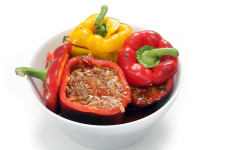 capsicums: A deep bowl containing peppers filled with minced beef, tomato, parsley, onion and rice, a traditional Greek dish called gemista, which can be made with or without meat