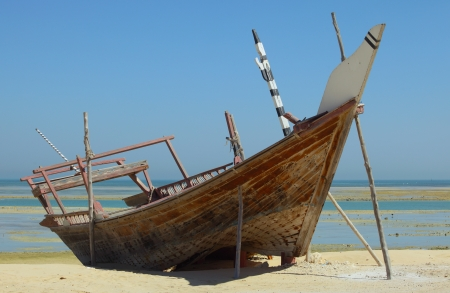 ship wreck: A beached dhow at Wakrah, south of Doha, Qatar  The vessel seems to have been abandoned long ago and is little more than a wreck now