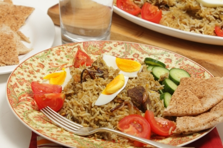 int: Beef biryani served with tomato, cucumber, flat bread and a glass of water, with the serving dish int he background