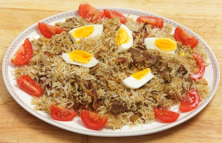 biryani: Homemade beef biryani garnished with egg, tomato and cucumber, on a serving dish