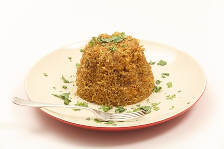 biryani: A plate of traditional Indian chicken biryani, garnished with coriander  cilantro  and mint leaves on a plate with a fork