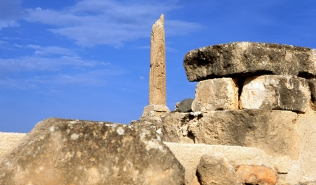 A lone pillar of the prehistoric Greek temple to Apollo stands amid the ruins of ancient Aegina, a stone photo