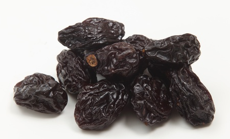 laxative: A close-up view of a pile of prunes on a white background