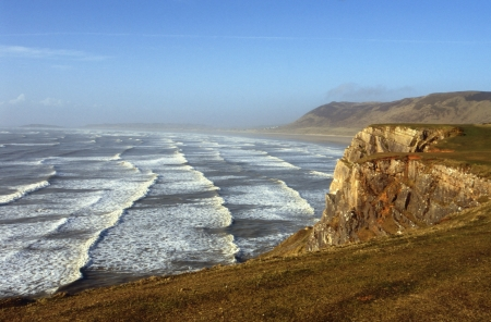bristol channel: Lines of surf roll in to Rhossili Beach  or Llangenneth Sands , on the Gower Peninsula in South Wales, UK  The three-mile wide beach is the largest of many popular surfing destinations on the picturesque peninsula