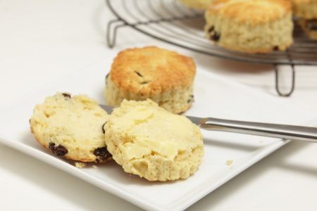 teacake: Freshly-baked fruit scones, with one on a plate cut open and buttered  Scones - similar to American  biscuits  are a traditional British tea-cake