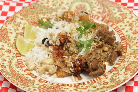 Adinner plate of home-made biryani-type fragrant lamb curry, cooked with dried apricots and yoghurt and garnished with toasted cashews, fried onions and coriander, served with cardamom-flavoured basmati rice  photo