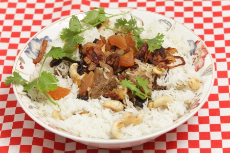 A serving bowl of home-made biryani-type fragrant lamb curry, cooked with dried apricots and yoghurt and garnished with toasted cashews, fried onions and coriander, served with cardamom-flavoured basmati rice  photo
