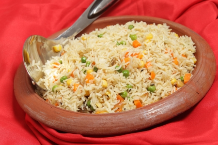 Vegetable pilau, or pulau, rice in an ethnic indian terracotta clay bowl with a rice serving spoon