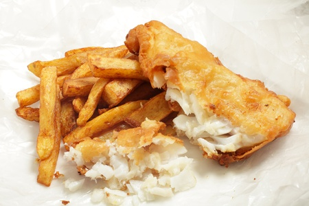 battered: British  chip shop  style fried cod in batter with chips  french fries  in a wrapping of greaseproof paper  Shot with a tilt-shift lens for maximum depth of field