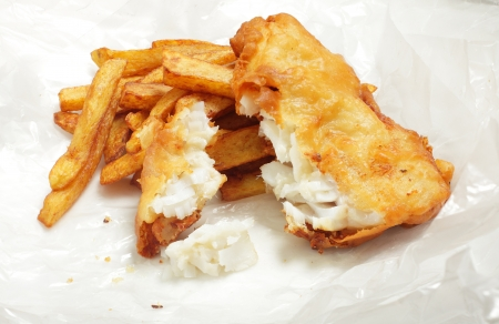 British  chip shop  style fried cod in batter with chips  french fries  in a wrapping of crumpled greaseproof paper  Shot with a tilt-shift lens for maximum depth of field  photo