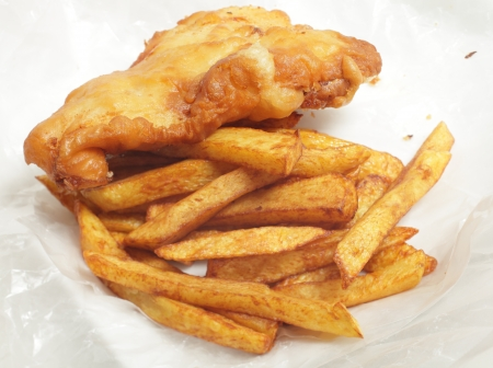 British  chip shop  style fried cod in batter with chips  french fries  in a wrapping of greaseproof paper  photo