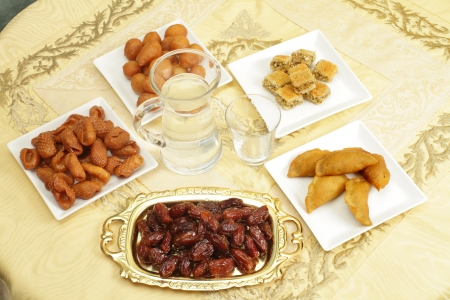 A table set for Iftar, the fast-breaking during the Muslim holy month of Ramadan, with dates and water as well as a variety of Middle Eastern sweet treats. From the bottom, clockwise, dates, Asabe zeinab or Zeinabs fingers, Awama, kunafeh stuffes with cho