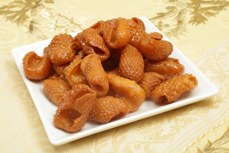 particularly: Asabe zeinab or Zeinabs fingers on a plate. This  Middle Eastern sweet treat made of a semolina yeast dough, formed into this shape and coated in syrup. It is particularly popular in Ramadan. Stock Photo