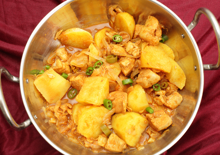 chicken curry: A vindaloo chicken and potato curry, cooked balti-style in a kadai  karahi  cooking pot, garnished with sliced chillis