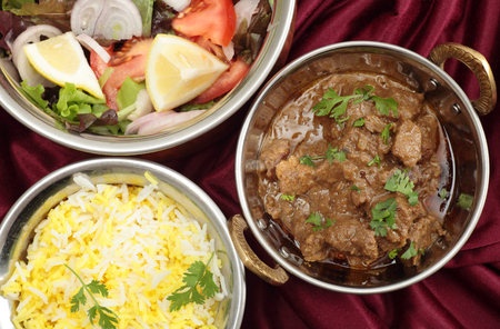 gosh: Indian copper dishes with homemade beef rogan josh, white and yellow rice and a salad, seen from above