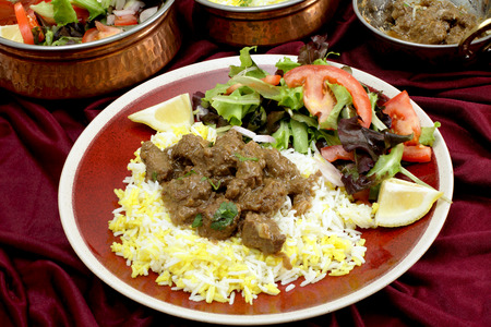 A plate of  homemade beef rogan josh, served with yellow and white rice and a salad, with typical Indian serving bowls behind  Rogan josh is usually made with lamb photo