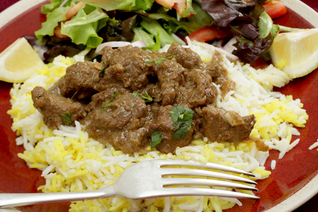 gosh: A plate of  beef rogan josh, served with yellow and white rice and a salad  Rogan josh is usually made with lamb, as it is a Hindu dish, but works equally well with beef