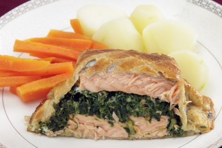 wellington: Salmon fillet stuffed with a spinach mixture and encased in puff pastry, served with boiled new potatoes and julienned carrots   Stock Photo