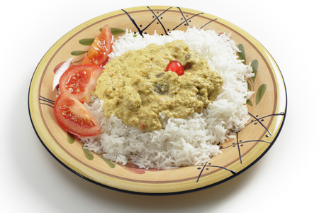 Mutton muglai curry, a restaurant verstion of a traditional Hyderabadi recipe, served on Basmati rice with tomato wedges, photo