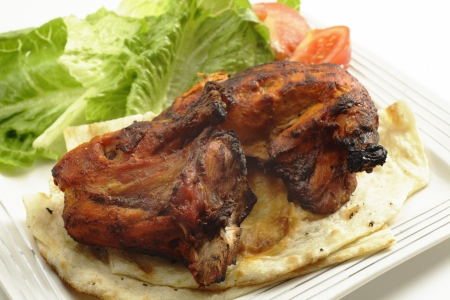 tandoori chicken: Traditional indian tandoori chicken pieces, served on flat bread with a salad and tomatoes, side view, a delicacy from the Punjab region of north India and Pakistan