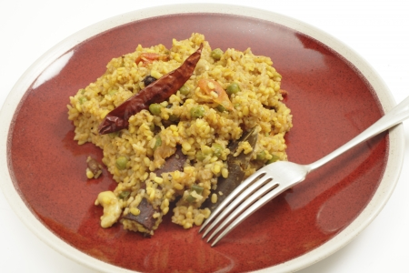 bengali: Bengali kichuri on a plate with a fork, side view  Kichuri, which gave rise to English kedgeree, is a popular Bangladeshi and North Indian breakfast, made from rice, moong dal, vegetables, fruit, nuts and spices