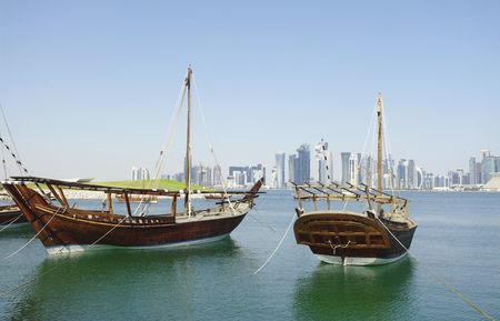 postmodern: Traditional wooden dhows moored off Museum Park, Doha, Qatar, with the citys postmodern 21st Century high-rise skyline beyond.