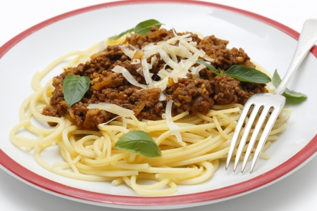 Spaghetti served with a homemade bolognese sauce, incorporating tomato puree, minced beef, wine, pine-nuts, onion, garlic, oregano, allspice, salt and pepper, and topped with parmesan cheese and fresh basil leaves.
