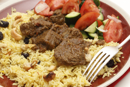 Close-up view of a homemade beef madras curry served with saffron, raisin and roast cashew nut pilau rice and a salad of tomato, cucumber and shallots. photo