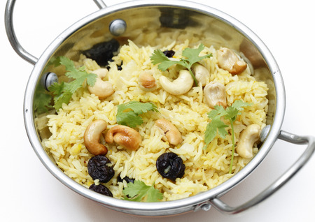 Raisin and cashew pilaf, made with basmati rice and garnished with coriander leaves, served in a traditional indian kadai dish photo