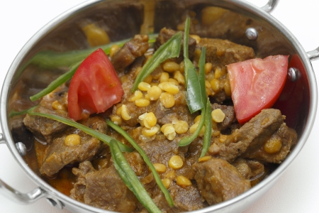 Lahore (Pakistan) style lamb and Chana dhal (split pea) curry, garnished with sliced chillies and chopped tomato, in a kadai serving bowl photo