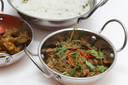A bowl of spiced lamb curry with coriander leaves and slivers of red and green chillies, next to a bowl of Lahore-style lamb curry with split peas and some rice. photo