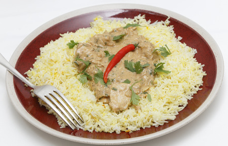 High angle view of balti chicken pasanda curry served on a bed of saffron rice, garnished with coriander leaves and a red chilli. This curry is made with yoghurt , cream and chopped coriander as well as the usual spices, to give a fairly mild and creamy f photo