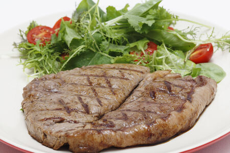 Low-carb meal of grilled rump steak with a home-grown salad mix and cherry tomatoes photo