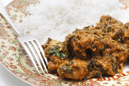 fenugreek: Methi murgh - chicken cooked with fresh fenugreek leaves on a plate with basmati rice and a fork Stock Photo