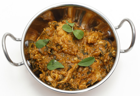 fenugreek: Methi murgh - chicken cooked with fresh fenugreek leaves - in a kadai, or karahi, traditional Indian wok, over white, garnished with fenugreek leaves and seen from above