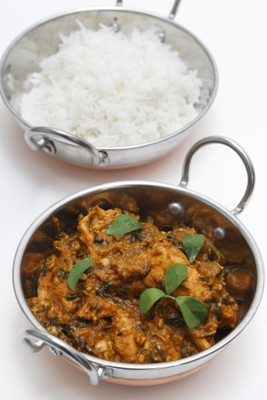 Methi murgh - chicken cooked with fresh fenugreek leaves - in a kadai, or karahi, traditional Indian wok, over white, garnished with fenugreek leaves, next to a bowl of basmati rice and seen from above photo