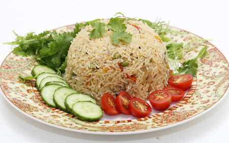 incorporates: A healthy tomato (thakkali) biriyani with a salad of cucumber, cherry tomatoes and some fresh leaves. This biryani, which incorporates onion, peas and a capsicum  ball pepper, is a South Indian dish. Stock Photo