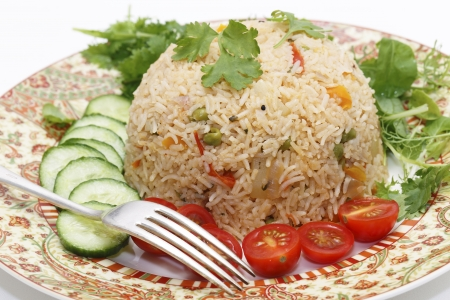 biryani: A healthy tomato (thakkali) biriyani with a salad of cucumber, cherry tomatoes and some fresh leaves, closeup with a fork. This biryani, which incorporates onion, peas and a capsicum  ball pepper, is a South Indian dish.