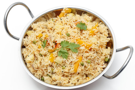 biryani: A kadai (karahi or wok) full of healthy vegetarian tomato biryani (thakkali biryani) in the South Indian style, containing onion, peas, tomato, bell pepper and onion seeds.
