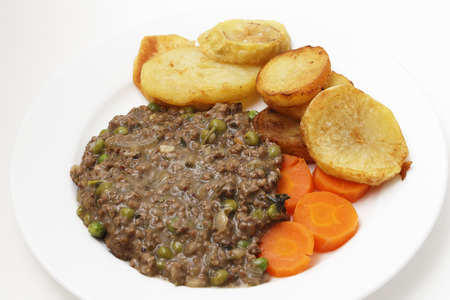 sautee: Minced beef cooked with onion, garlic, peas and herbs, served with sautee potatoes and boiled carrots  This is a simple, slightly old-fashioned British-style meal, high angle Stock Photo