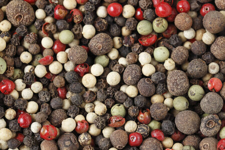 A mixture of different kinds of peppercorns, including black, white, green, grey, pink and Jamaican pepper - or allspice  photo