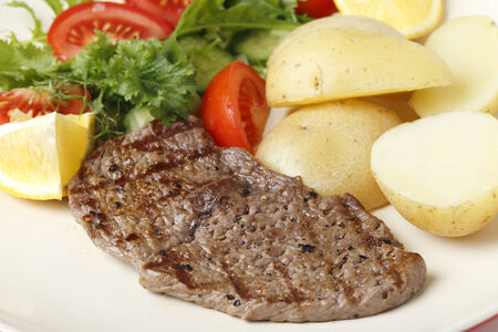 balanced diet: Pan-grilled pepper minute steak served with a salad of fresh leaves, tomato, cucumber and lemon with boiled new potatoes