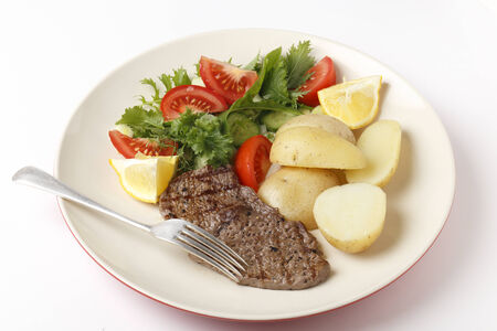 Pan-grilled pepper minute steak served with a salad of fresh leaves, tomato, cucumber and lemon with boiled new potatoes photo