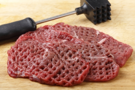 steak beef: Three raw minute steaks displayed next to a meat mallet after being pounded and tenderised Stock Photo