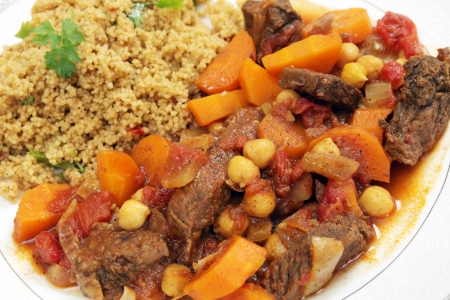 Plate of traditional Moroccan beef tagine with couscous, garnished with flat-leaf parsley photo