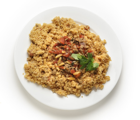 incorporates: A plate of Lebanese burghul bi banadoura, or cracked wheat with tomatoes  The dish incorporates onion, minced meat and pine nuts, along with the burghul or bulgar wheat from above