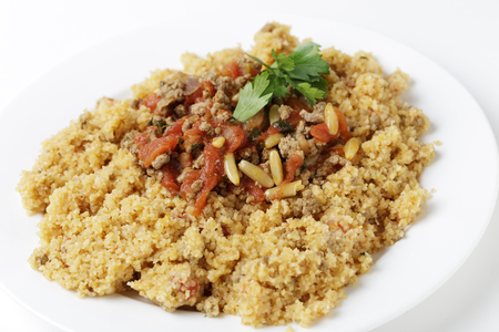 incorporates: A plate of Lebanese burghul bi banadoura, or cracked wheat with tomatoes  The dish incorporates onion, minced meat and pine nuts, along with the burghul or bulgar wheat