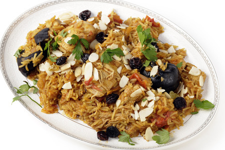 chicken rice: An authentic Saudi chicken kabsa (known in Qatar as majbous), garnished with raisins and toasted almond flakes, on a serving bowl. Kabsa is a national staple for Saudi Arabia and the Arab Gulf States.